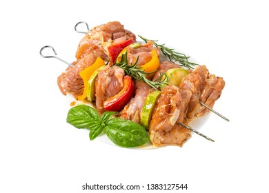 skewers of raw meat and vegetables in marinade on the plate isolated on white background. grill barbeque