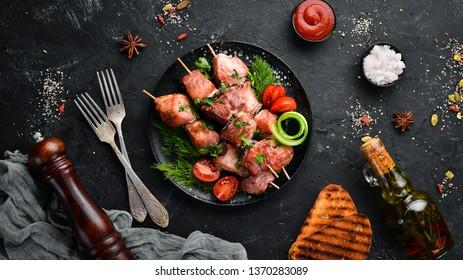 Skewers with vegetables. Kebab in a black plate. Top view. Free copy space.