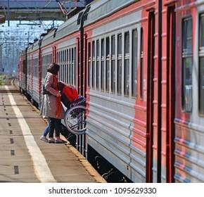 Skhodnya, Russia - May 09. 2018. man in wheelchair enters a train
