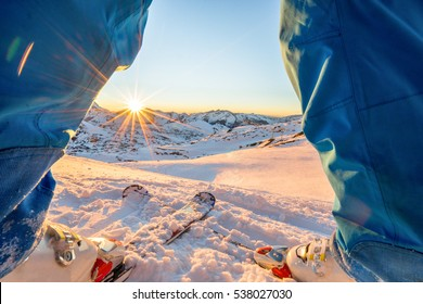 Ski athlete standing in front of wonderful sunset  on top of the mountain - Legs view of young skier with sun back light - Sport and vacation concept - Focus on skis - Warm filter