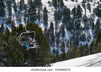 Ski chair lift with skiers on the background of fir trees