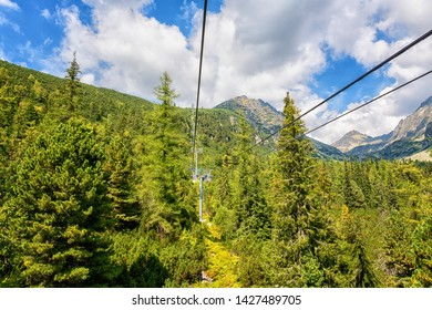 Ski chair lift in summer High Tatra mountains, scenic landscape with rocks, green trees and blue cloudy sky, outdoor travel background, Strbske Pleso region, Slovakia (Slovensko)