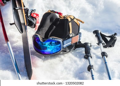 Ski gear on snow with reflection in the ski helmet visor.  The reflection in the visor is blue.  Ski poles are lying on the snow next to skis.