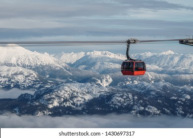 ski gondola with mountains in the background on a cloudy winter day