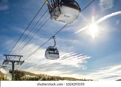 Ski gondola moving across the blue sky; sunlight lights the scene