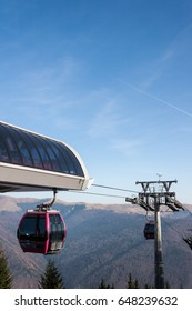 Ski gondolas on a mountain resort in bright sunlight.
