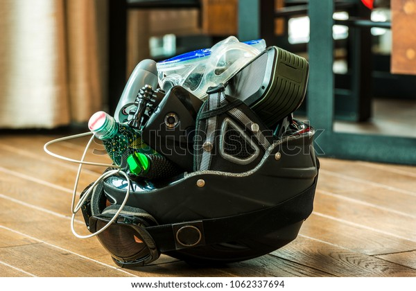 the ski helmet lies on the floor and is full of various different things