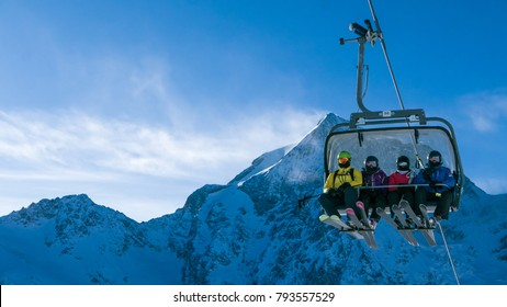 Ski holiday - family of skiers on chairlift in high Alpine ski r