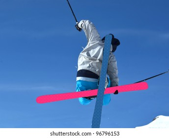 Ski Jumper performing a tele-heli and grab, with crossed skis