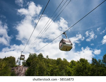 Ski lift against a cloudy blue sky.