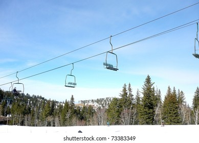 Ski Lift with Blue Sky, Forest, and Snowy Slope