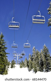 Ski lift chairs against blue sky