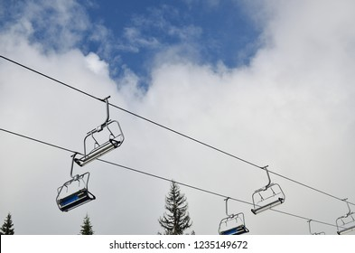 Ski lift chairs with no one on them - against cloudy sky