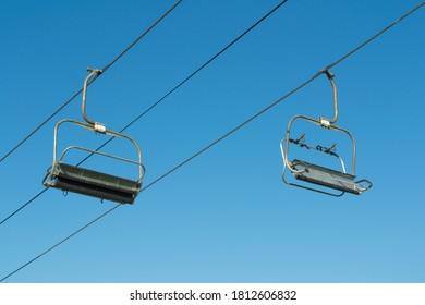 Ski lift chairs in summer on blue sky