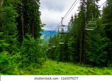 Ski lift in the rainy summer mountains through amazing fabulous moutain forest in Bukovel, Ukrainian Carpathians