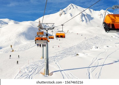 Ski lift ropeway on hilghland alpine mountain winter resort on bright sunny day. Ski chairlift cable way with people enjoy skiing and snowboarding.Banner panoramic wide view of downhill slopes