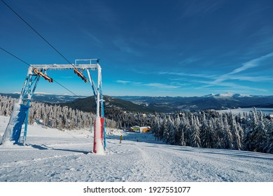 Ski lift with seats going over the mountain and paths from skies and snowboards.