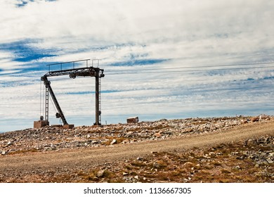 Ski lift tower and a wooden cart on top of the Ylläs fjell in the Finnish Lapland. The rocky terrain almost resembles a terrain of another planet.
