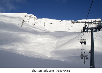 Ski lift with two skiers visible against a white snow slope and blue sky. Sunny winter day at First area near Grindelwald, Berner Oberland, Switzerland.