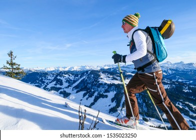 Ski mountaineer ascending in the mountains at a sunny day in late winter