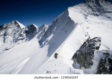 A ski mountaineer traversing a steep snowy ridge in the Alpds