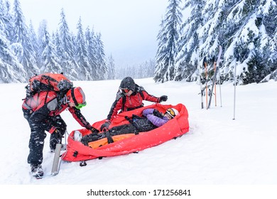 Ski patrol with rescue sled helping injured woman snow forest