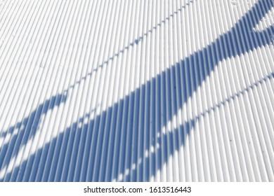 Ski piste with a shadow of a skier. Background ski piste.