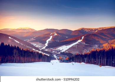 Ski resort in beautiful sunset light. View from the top: ski tracks, pine tree forest and mountains in the background. Winter holidays in Bukovel, Carpathians, Ukraine, Europe