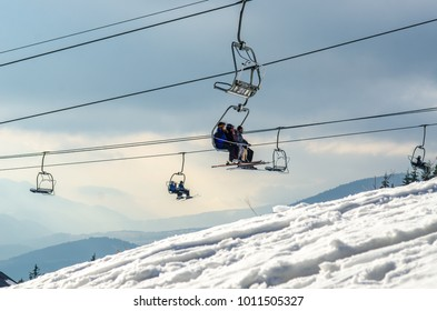 Ski resort. People on the ski lift at the mountains background