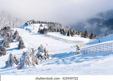 Ski resort, ski slope, ski lift, pine trees and fog mountains panorama