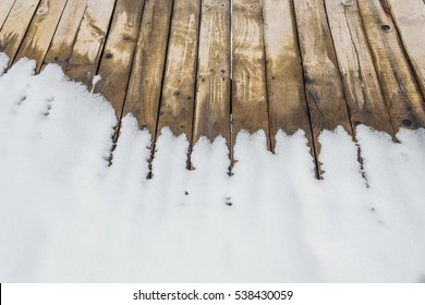 Ski resort. Wooden floor, covered with remnants of melting snow. Rustic background.