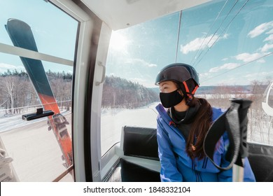 Ski resorts open for winter sports following coronavirus restriction guidelines. Woman tourist wearing face mask inside cabin lift on mountain slope going skiing.