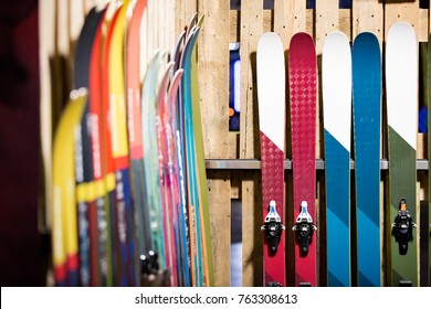 Ski shop sale. Rows of  colourful skis on wooden wall.