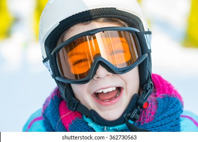 Ski, skier girl, winter vacation, snow, skier, sun and fun - portrait of happy girl in goggles enjoying ski