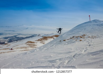 Ski slope. Armenia. Snowboarder  jumping from the mountain to the snow slope. A Sunny day in the mountains of Tsaghkadzor on the background of blue sky. Russia