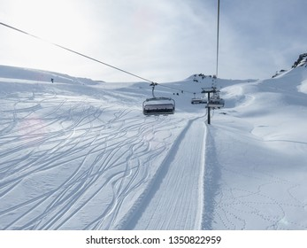 Ski slope lift ride upwards. Amazing sunny day on Austrian ski slopes. Beautiful and perfectly prepared slopes or freeride hills. Cable car with a cabin, typical winter way of transport.
