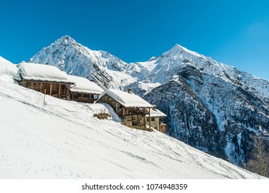 Ski slope next to the traditional chalet covered with snow. Mountain Landscape in Winter. Monterosa Monte Rosa Masif, Gressoney, Italy. Italian Alps. Epic winter landscape in the high mountain