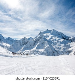 Ski slope, Peak Ine and Mt. Sofrudzhu in winter sunny day. Dombay ski resort, Western Caucasus, Russia.