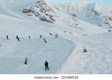 Ski slope with skiiers, and a snowboarder tumbling.