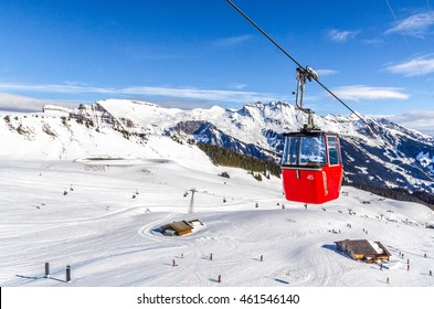 ski slope in Swiss Alps in sunny day. Red cable car above and mountains behind, skiing resort, Switzerland.