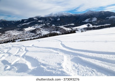 Ski slope with ski tracks - beautiful winter day - view from the mountain top to the valley
