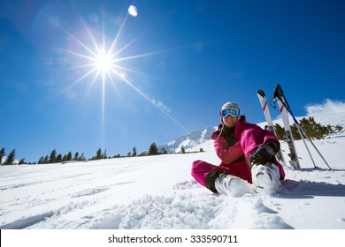 Ski, snow and sun - resting female skier in winter resort