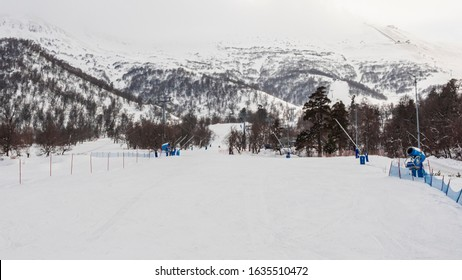 Ski and snowboard hill covered with snow. Blue protection net and artificial snow machine