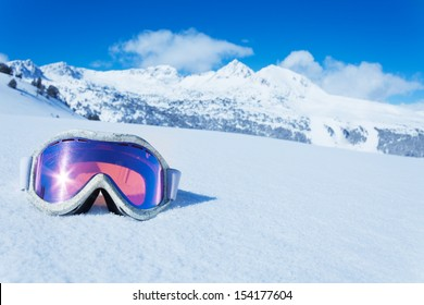 Ski and snowboard mask in the snow with copy space and mountain on background