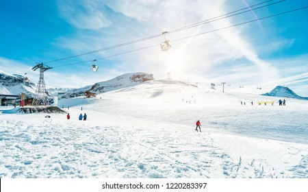 Ski and snowboard sport resort for winter vacation with cable car in background - Holidays and mountain landscape concept - Focus on skier with red jacket