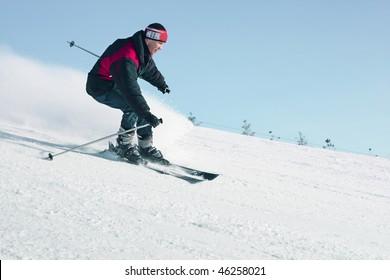 Ski sportsmen in motion over clear blue sky