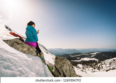 A ski tourer girl having a snack in the mountains in winter snowy landscape