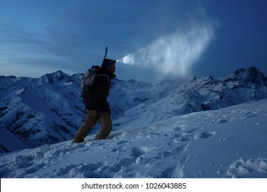 Ski touring man commit climb on night winter mountain. Tourist with headlamp, backpack and a snowboard behind his back walking on snowy slope. Backcountry