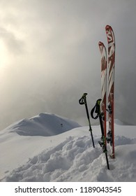 Ski touring with Salomon Ski and Leki poles at Strimskogel summit with ridge in warm misty light and light snowfall