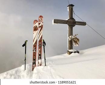 Ski touring summit with Salomon Ski, Leki poles and summit cross in winter at Strimskogel Alps in warm misty light